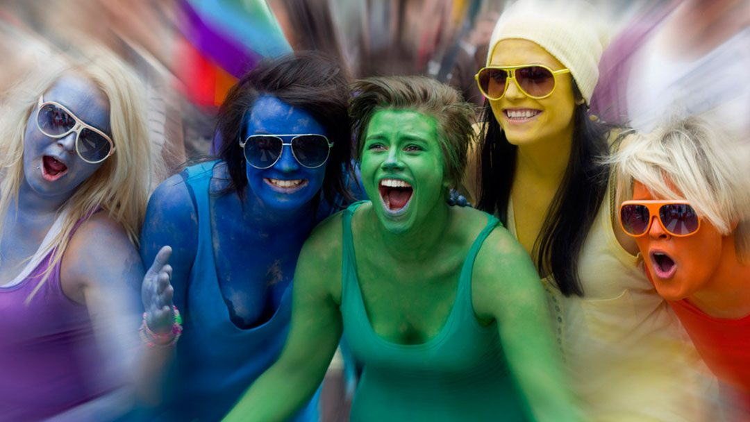 Excited women painted in rainbow colors against blurry background; photo by Tjook on Flickr